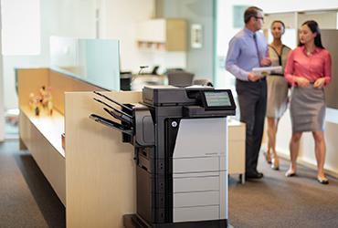 Coworkers walk by an HP Laserjet MFP 630 printer in an office.